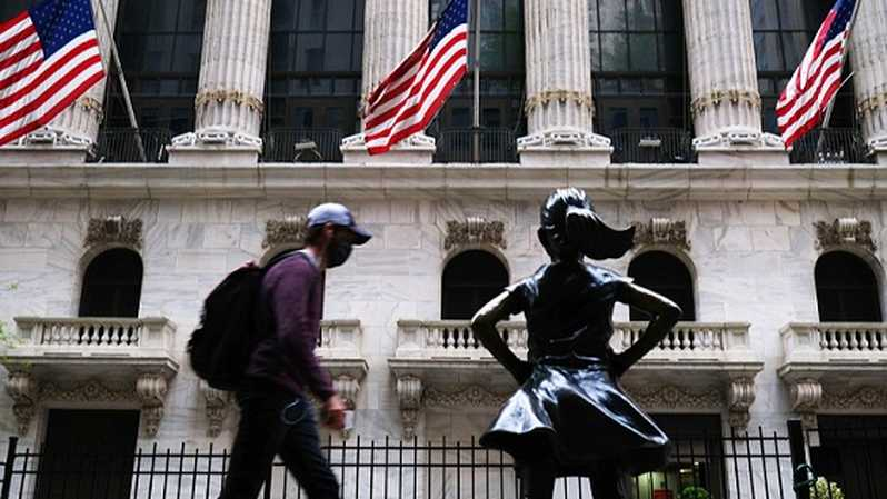 Pejalan kaki melintas di depan Bursa Efek New York (NYSE), AS. Foto: Spencer Platt / Getty Images / AFP