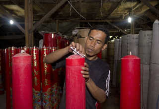 A worker files the tip of an oversized candle at a factory in Teluk Naga, Tangerang, on Wednesday (18/01). The factory produces candles up to 1.5-meter high. (JG Photo/Yudha Baskoro)
