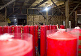 Finished candles are wrapped in plastic, which often features dragon ornaments, at a factory in Teluk Naga, Tangerang, on Wednesday (18/01). The factory produces candles of various dimensions, from 15 kg in weight up to more than a tonne. (JG Photo/Yudha Baskoro)