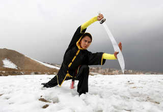 Sima Azimi, 20, a trainer at the Shaolin Wushu club, shows her Wushu skills to other students on a hilltop in Kabul, Afghanistan January 29, 2017. euters Photo/Mohammad Ismail