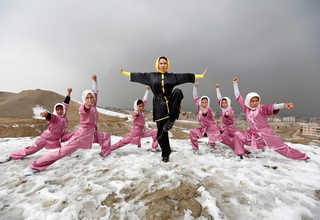 Sima Azimi (C), 20, a trainer at the Shaolin Wushu club, poses with her students after an exercise on a hilltop in Kabul, Afghanistan January 29, 2017. euters Photo/Mohammad Ismail