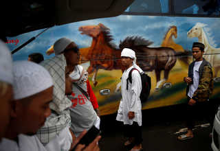 """Protesters walk after praying during a rally against Jakarta Governor Basuki """"Ahok"""" Tjahaja Purnama in front of the Istiqlal Mosque in Jakarta on Saturday (11/02). (Reuters Photo/Beawiharta)"""