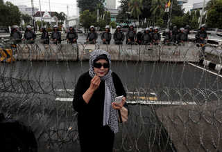 A female protester stands near barbed wires as she heads to the Istiqlal Mosque on Saturday (11/02) to pray during a rally against the Jakarta governor. (Reuters Photo/Beawiharta)