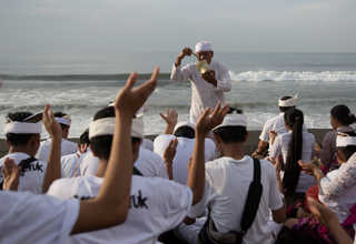 A Balinese Hindu priest sprinkled water on people praying on a beach during Melasti, a purification ceremony ahead of the holy day of Nyepi, in Gianyar, Bali, Indonesia on Saturday (25/03). (Reuters Photo/Agung Parameswara)