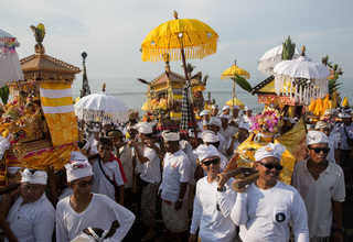 Balinese Hindu men carried Jempana, or symbols of God, along a beach during Melasti, a purification ceremony ahead of the holy day of Nyepi, in Gianyar, Bali, Indonesia on Saturday (25/03). (Reuters Photo/Agung Parameswara)