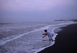 A Balinese Hindu woman collected sea water on a beach during Melasti, a purification ceremony ahead of the holy day of Nyepi, in Gianyar, Bali, Indonesia on Saturday (25/03). (Reuters Photo/Agung Parameswara)