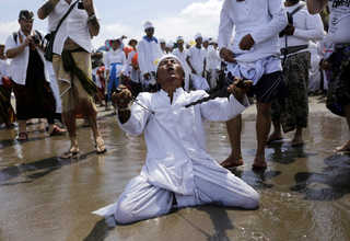 A Balinese Hindu worshipper attempted to stab himself with kris knives while in a trance on the beach during Melasti, a purification ceremony ahead of the holy day of Nyepi, in North Kuta, Bali, Indonesia on Saturday (25/03). (Reuters Photo/Nyimas Laula)