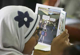 A schoolgirl is reading a comic book on credit cards during Digital Financial Literacy for Children class on Tuesday (04/04). (JG Photo/Yudha Baskoro)