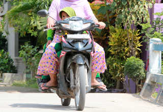 A young mother takes her daughter to school on a motorcycle in Menoro on April 19, 2017. Child marriage is one of the main causes of school dropouts in the area. (JG Photo/Yudhi Sukma Wijaya)
