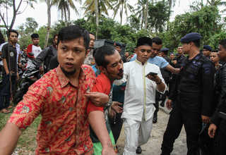 Plainclothes police officers, assisted by members of the local community, arrest an inmate who escaped from Sialang Bungkuk Prison in Pekanbaru, Riau, on Friday (05/05). (Antara Photo/Rony Muharrman)