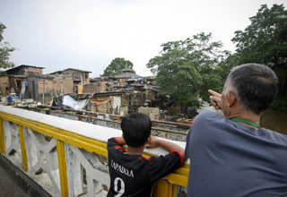 A boy and his grandfather watch as their neighbors strip their homes of any valuables before the Jakarta administration demolishes them. (JG Photo/Yudha Baskoro)