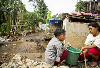 A boy and his mother fetch water in a pail from a public bathroom in Bukit Duri. (JG Photo/Yudha Baskoro)