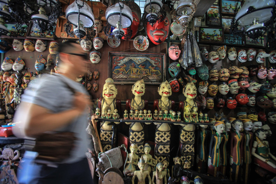 A visitor looks at antiques for sale at Windujenar market in Solo, Central Java. (Antara Photo/Maulana Surya)