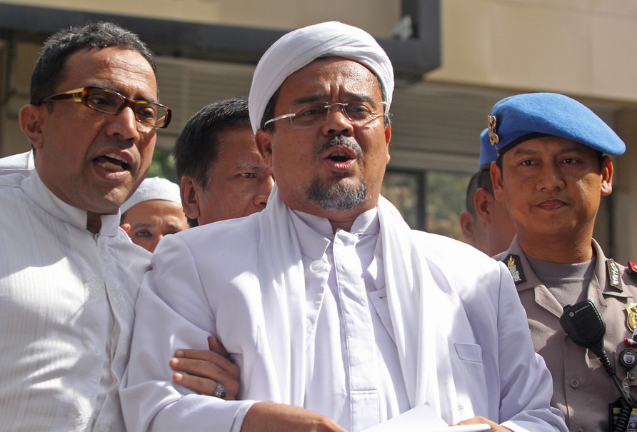 Islamic Defenders Front leader Rizieq Shihab, center, speaks to reporters after undergoing questioning at police headquarters in January. (Antara Photo/Reno Esnir)