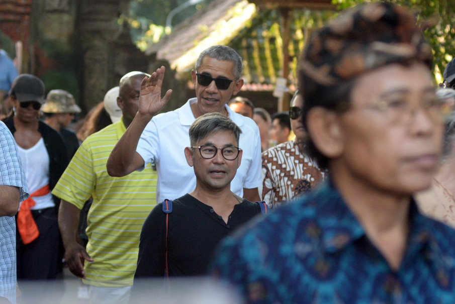 Former United States President Barack Obama waves to onlookers while visiting Tirta Empul Temple in Gianyar, Bali. (Antara Photo/Wira Suryantala)