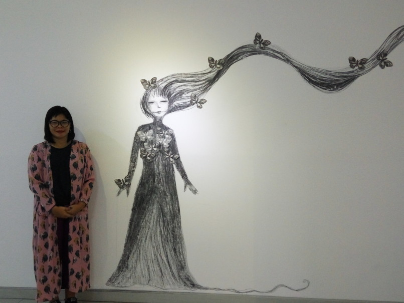 Daniella F. Praptono with one of her drawings titled 'Agreement of Hopes and Dreams.' (JG Photo/Dhania Sarahtika)