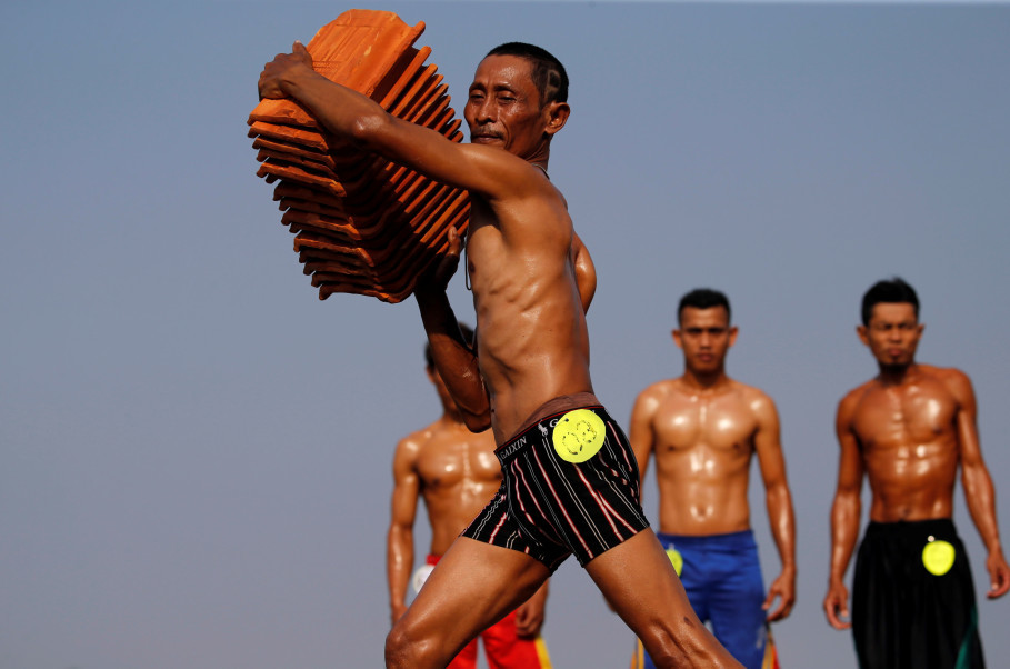 A worker lifts tiles during a bodybuilding contest for tile factory workers ahead of the Independence Day celebrations in Jatiwangi village in Majalengka, West Java, Aug. 11. (Reuters Photo/Beawiharta)