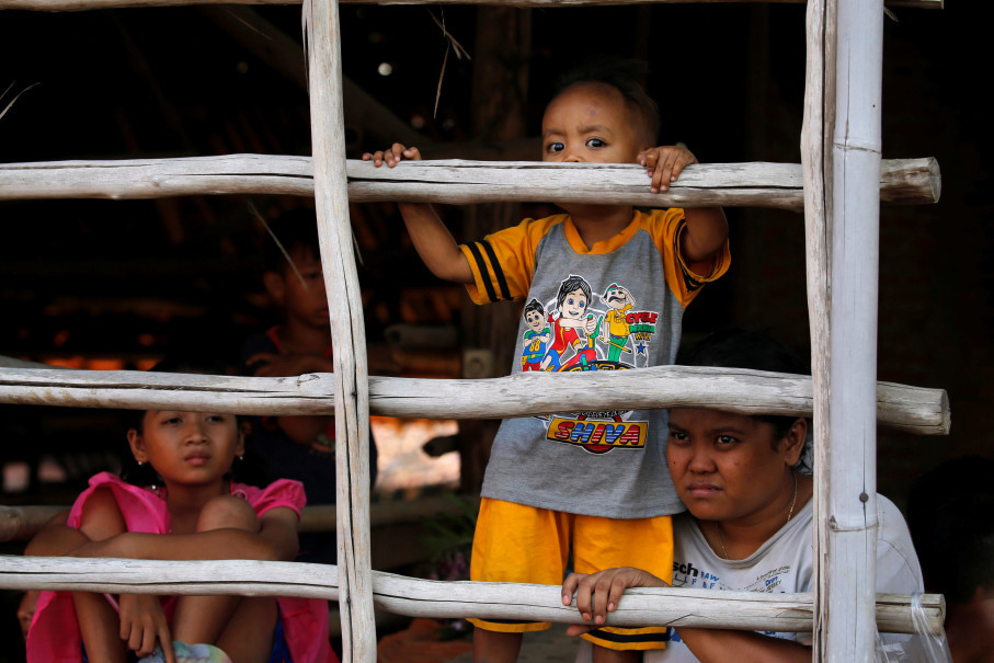 Children watch their fathers lift weights made of tiles during the  bodybuilding contest for tile factory workers organized at Jatiwangi village in Majalengka, West Java, on Aug. 11. (Reuters Photo/Beawiharta)