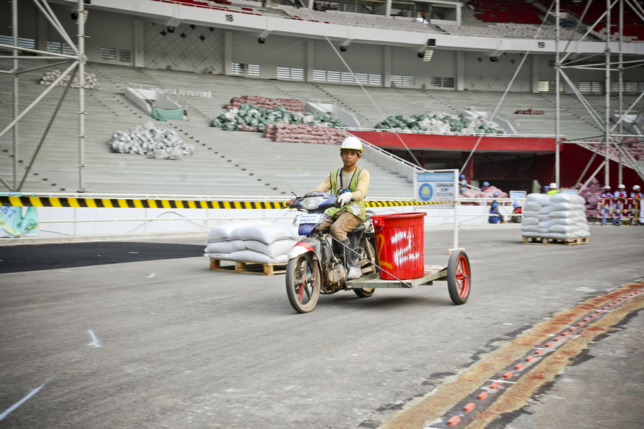 A worker rides a modified motorcycle to carry cement inside the stadium. (JG Photo/Yudha Baskoro)