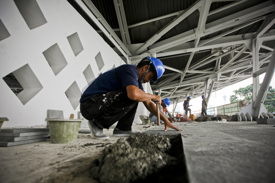 A worker attaches floor covering on the stadium's upper level. (JG Photo/Yudha Baskoro)