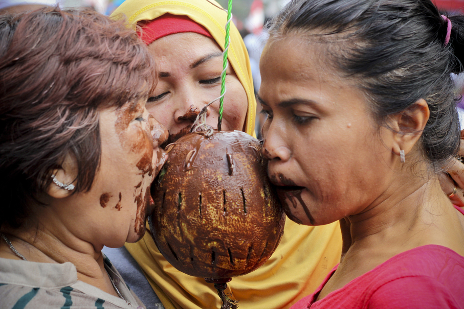 Women pick up coins from a chocolate-covered fruit during the Independence Day celebrations in Jalan Jaksa, Central Jakarta, on Thursday (17/08). (JG Photo/Yudha Baskoro)