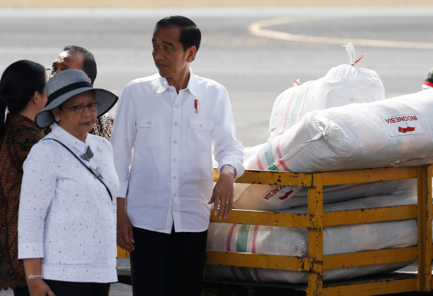 President Joko 'Jokowi' Widodo, center, and Foreign Minister Retno Marsudi, left, stand beside a cart filled with food aid for Rohingya refugees at Halim Perdanakusuma military airbase in Jakarta on Sept. 13, 2017. (Reuters Photo/Beawiharta)