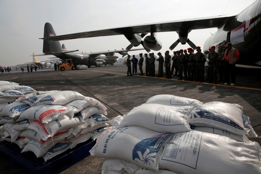 Volunteers wait next to sacks of rice and a Hercules C130 plane at Halim Perdanakusuma. (Reuters Photo/Beawiharta)