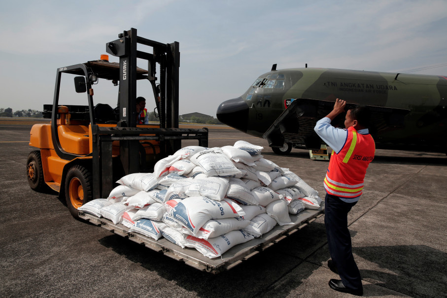 A forklift driver maneuvers bags of rice into a waiting transport plane. (Reuters Photo/Beawiharta)