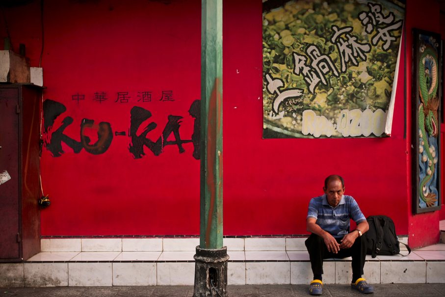 A man waits for a karaoke bar to open. (JG Photo/Yudha Baskoro)