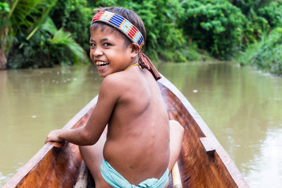 A Mentawai child rides a traditional wooden boat in the interior of Mentawai Islands. (Photo courtesy of Indigenous Education Foundation)