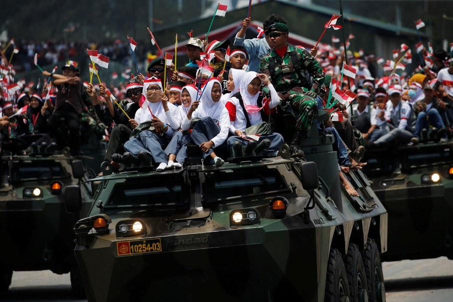 Students wave the national flag as they sit on top of an armored personnel carrier during the celebrations. (Reuters Photo/Beawiharta)