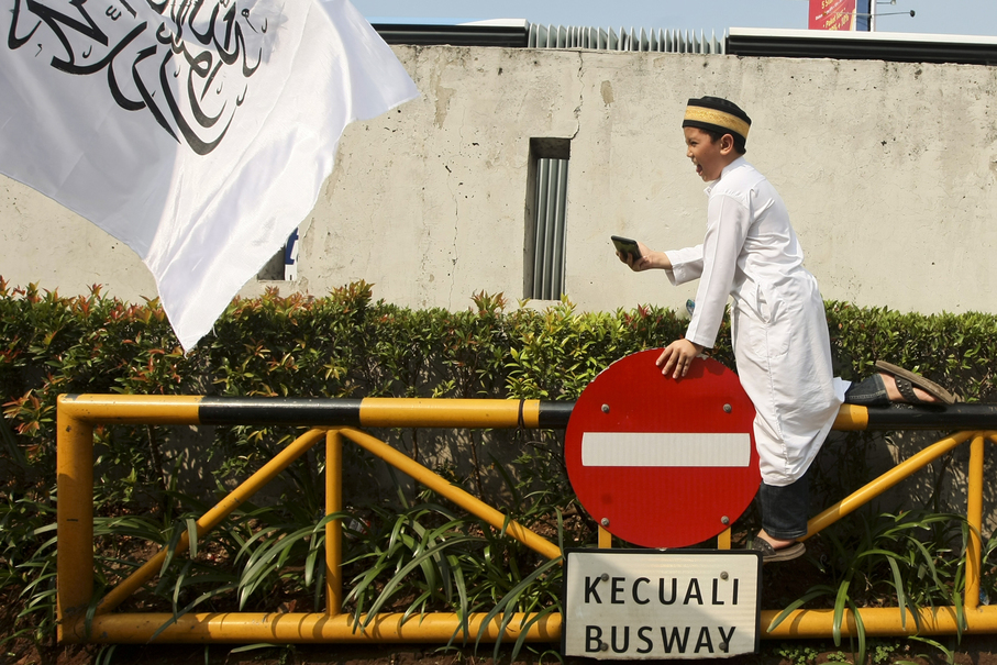 A boy joins the protest after performing his Friday prayer. (JG Photo/Yudha Baskoro)