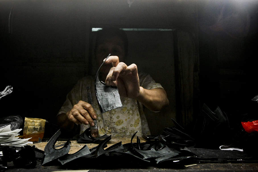 A worker glues together shoe soles at her home in Penjaringan, North Jakarta. (JG Photo/Yudha Baskoro)