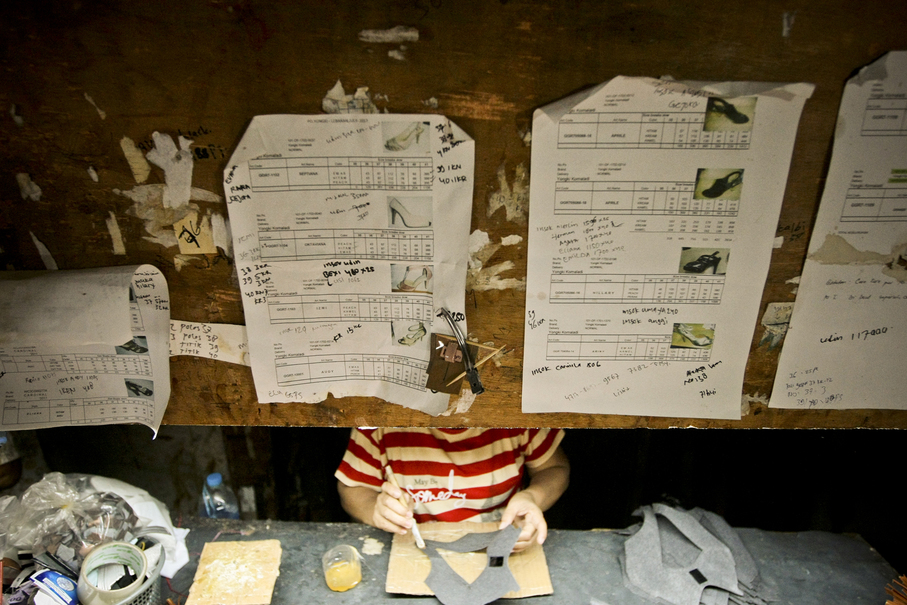 Designs of shoe models provided by local companies hang above a worker's desk at her home in Penjaringan, North Jakarta, on Thursday (05/10).