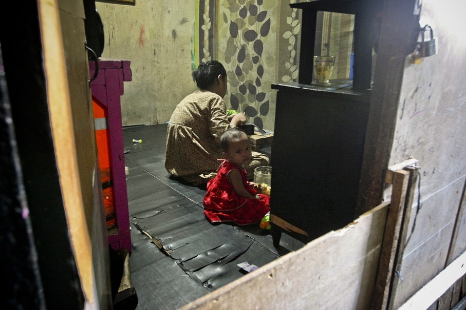 A child sits beside her mother, who is busy producing shoes for a local company, at their home in Penjaringan, North Jakarta, on Thursday (05/10).