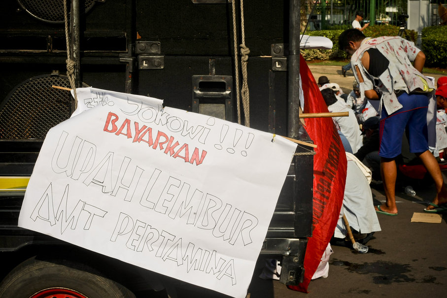 'Jokowi! Give us our overtime pay!' a poster says. (JG Photo/Yudha Baskoro)