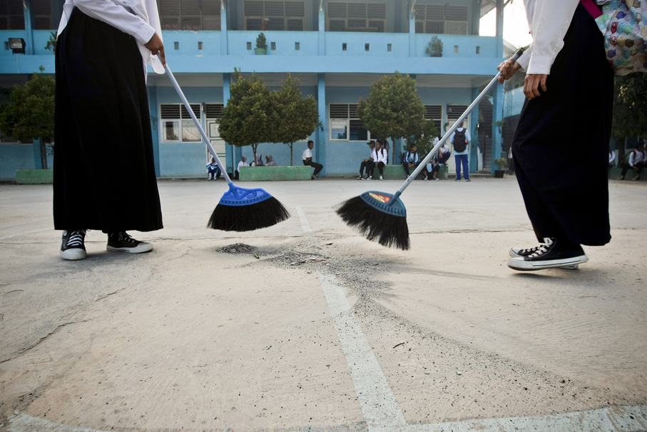 Children clean their school's courtyard of debris and pyrotechnic pellets. (JG Photo/Yudha Baskoro)