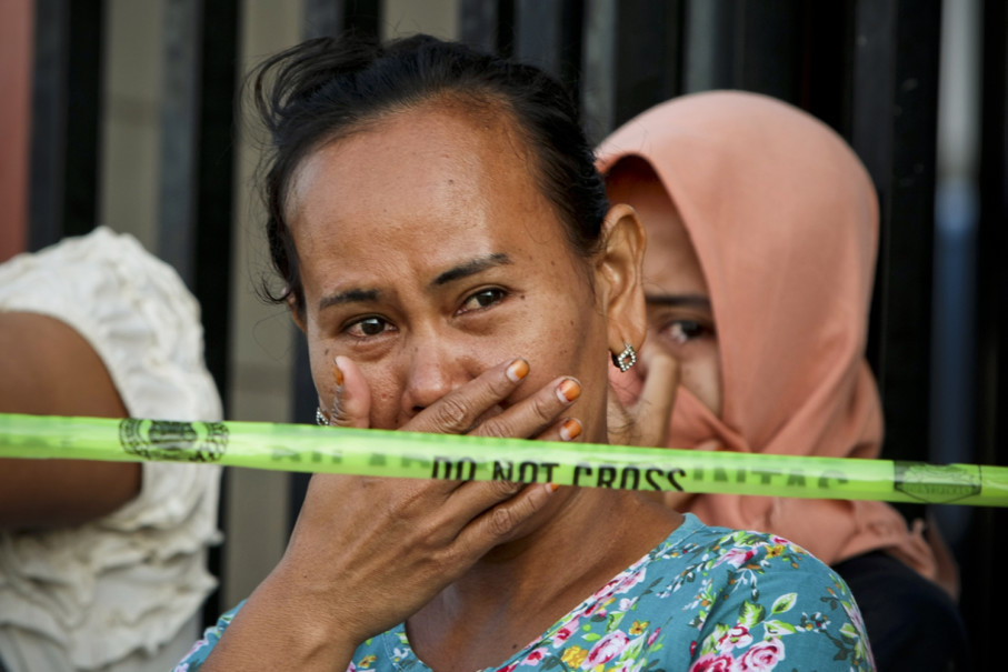 Women cry at the scene of the fire on Friday, hoping to learn from police officers that their relatives were not in the factory when the explosion occurred. (JG Photo/Yudha Baskoro)