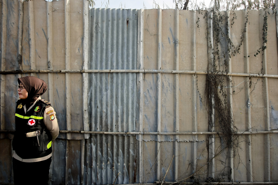 A police officer stands in front of the factory's wall. (JG Photo/Yudha Baskoro)