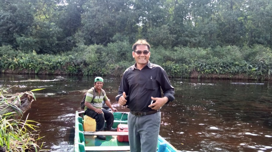 Mahyuddin Pasaribu standing on one of his pompong, or motorboats. (JG Photo/Muhamad Al Azhari)