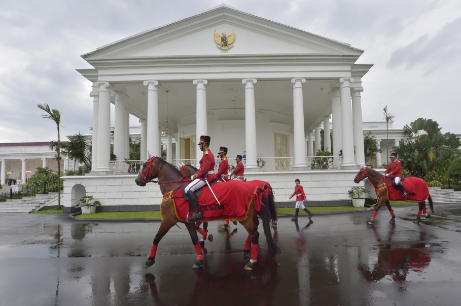 Horse-mounted presidential security guards (Paspampres) pass in front of the Bogor presidential palace. (Reuters Photo/Adek Berry)