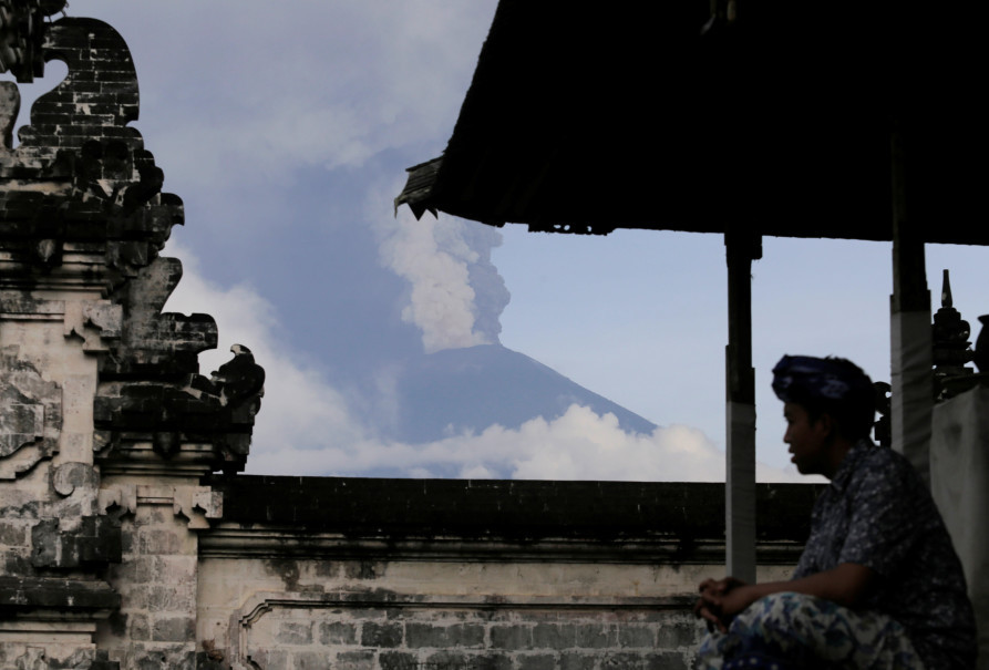 A man prays at Lempuyang Temple in Karangasem, Bali, on Nov. 27, 2017, as Mount Agung spews cold lava and ash cloud in the background. (Reuters Photo/Johannes P. Christo)