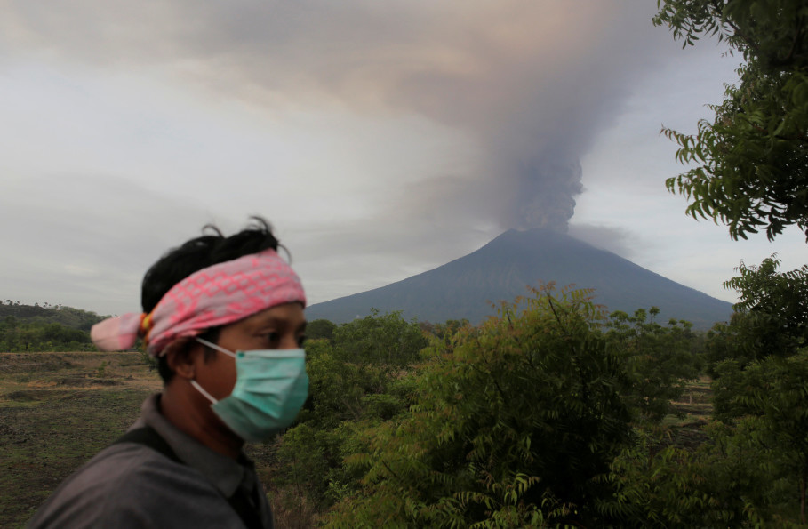 A villager in Kubu near Karangasem in Bali walks as Mount Agung volcano erupts in the background on Nov. 27, 2017. (Reuters Photo/Johannes P. Christo)
