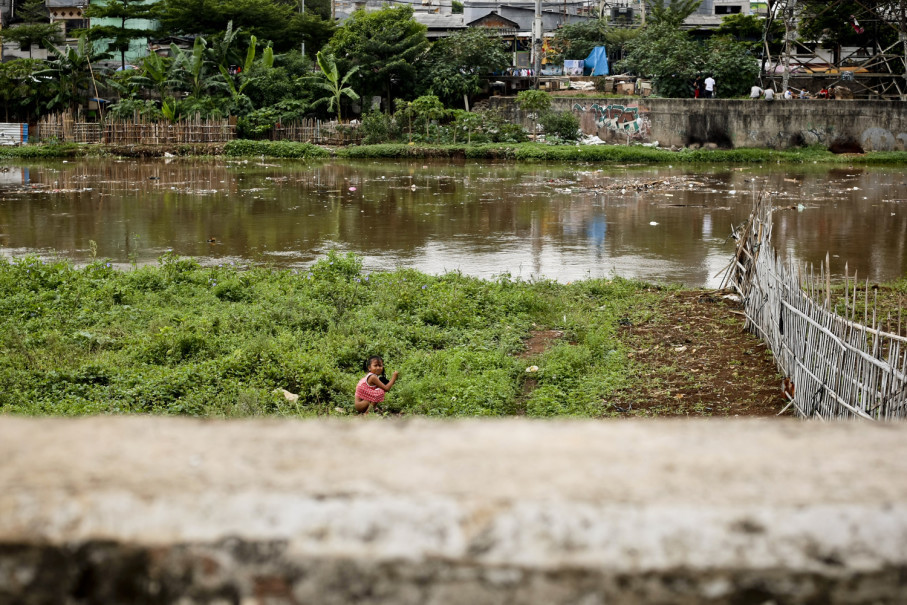 A girl relieves herself in a garden patch on the banks of the Western Flood Canal. (JG Photo/Yudha Baskoro)