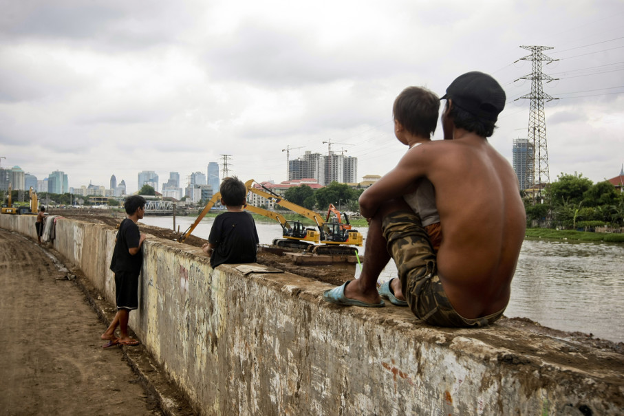 Children watch floating diggers clean up mud from the canal. (JG Photo/Yudha Baskoro)