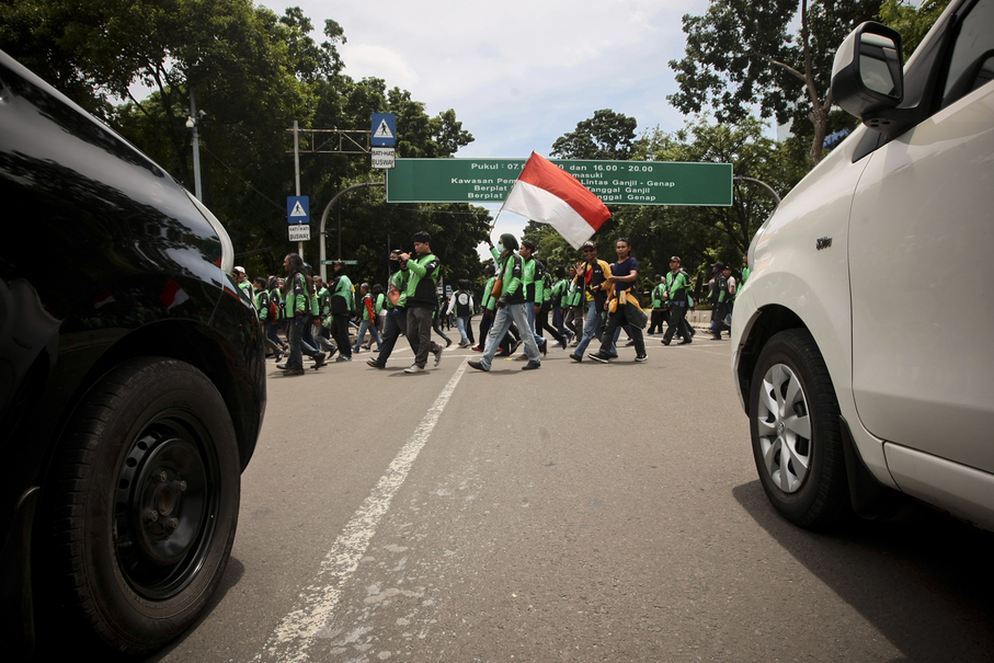Protesters cross the road outside the State Palace in Central Jakarta on Thursday. (JG Photo/Yudha Baskoro)