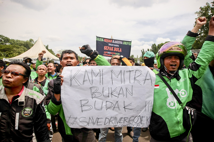 A protester holds up a poster saying: 'We are partners, not slaves.' (JG Photo/Yudha Baskoro)