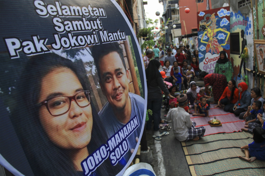"Residents put up posters to welcome the ""first family couple."" (Antara Photo/Maulana Surya)"