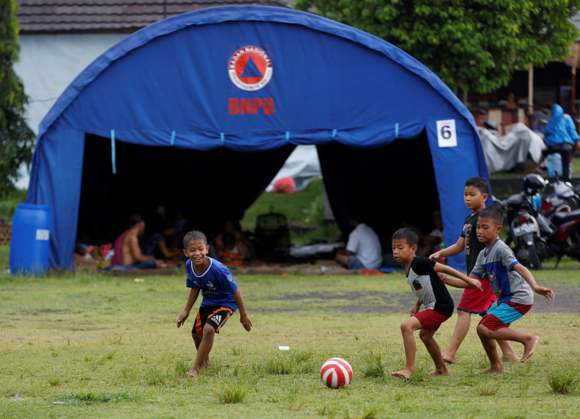 Children, who along with their families have been evacuated from areas near the volcano, play football at a shelter in a sports arena in Klungkung. (Reuters Photo/Darren Whiteside)