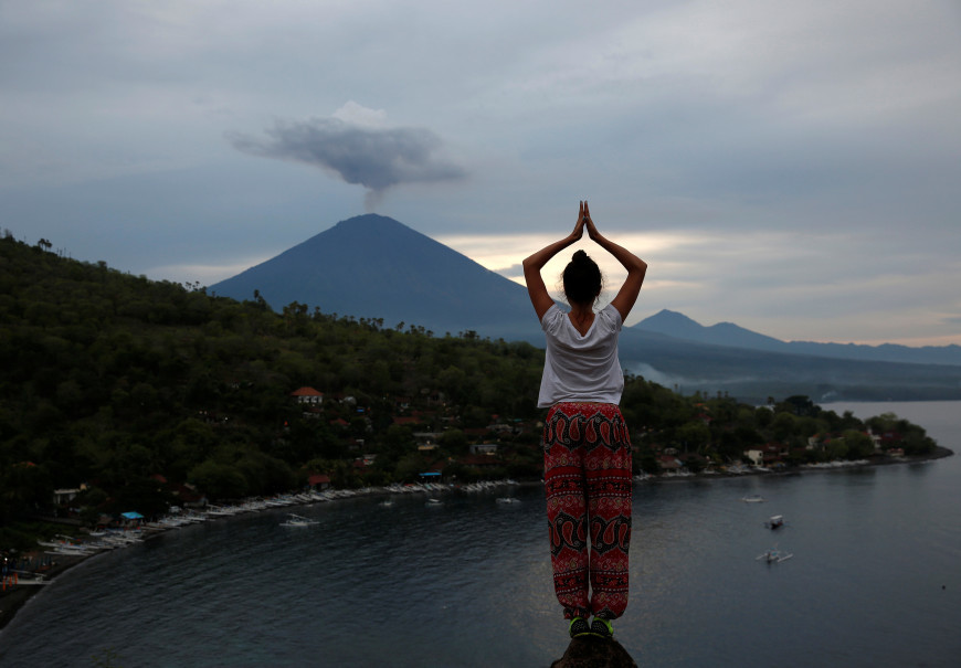 A tourist from poses while a friend takes her photograph with Mount Agung volcano erupting in the background from Amed, Karangasem, Bali. (Reuters Photo/Darren Whiteside)